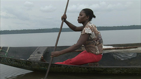 Layefa Malemi paddling in the Niger Delta. Gas flares and pollution from Shells oil drilling are destroying the local environment.