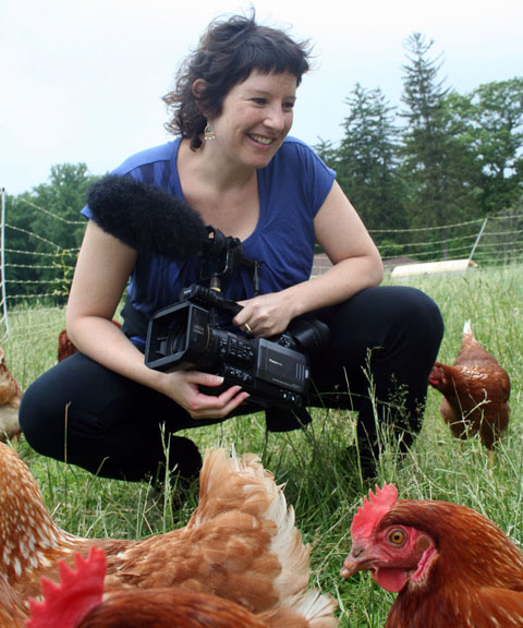 Director/producer Ana Sofia Joanes with hens in the field.
