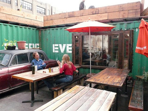 Diners in Roberta's backyard, and the green shipping containers that house HRN. Photo via Brooklyn Based.