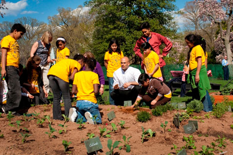 First Lady Michelle Obama and White House Chef Sam Kass show students from the Bancroft Elementary how to plant a garden. Photo: The White House.