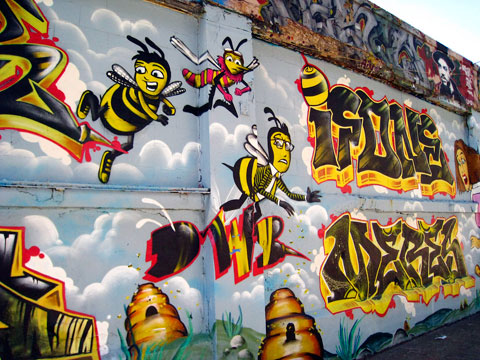 NYC bees no longer have to fear the law. Bee attack graffiti by Ifone & Meres. Photo by shoehorn99, Creative Commons.