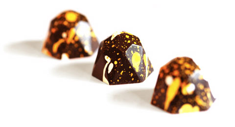 The pretty ginger truffles are made from 66% dark chocolate, splattered with cocoa butter colored with bright, natural colors, and filled with a ganache made from organic cream infused with fresh organic yellow ginger from Puna, Hawaii.