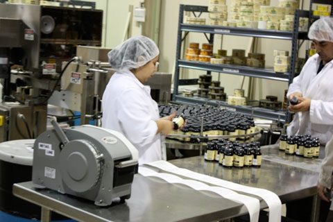 Workers putting labels on vanilla extract at the Nielsen-Massey factory in Waukegan, IL.