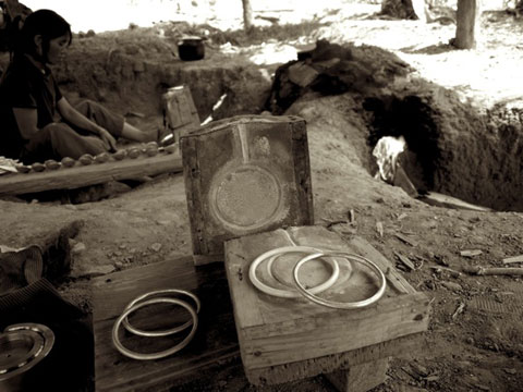 Wood and ash molds in front of an earthen kiln.