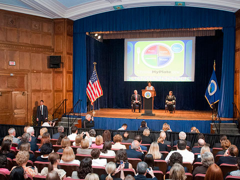 First Lady Michelle Obama talks about the new Food Icon MyPlate (L to R seated Agriculture Secretary Tom Vilsack and Surgeon General Regina Benjamin) on Thursday, June 2, 2011 in the Jefferson Auditorium, USDA.