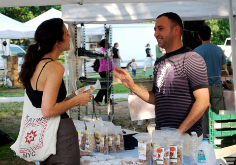 One of the refugees employed by The Providence Granola Projects chats with a customer at the Farmer's Market.