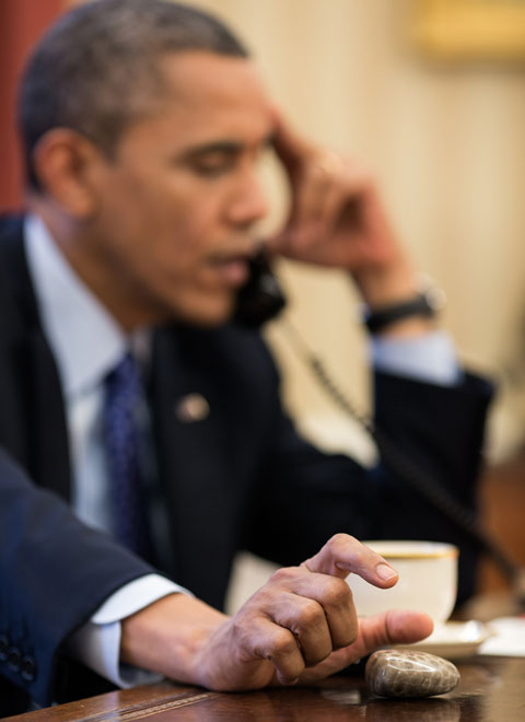 President Barack Obama plays with a Petoskey stone as he talks on the phone in the Oval Office, Dec. 6, 2012. Official White House Photo by Pete Souza, via The White House.