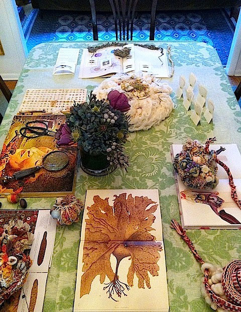 Recycled fiber forms by Abigail Doan are installed on the dining table with vintage textiles, botanicals, scientific/fashion prints, maker tools, and organic perfume by Lalun Naturals.